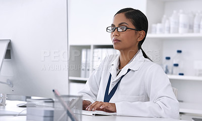 Buy stock photo Cropped shot of an attractive young female scientist working on her computer in the laboratory