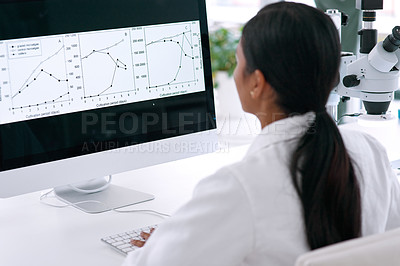 Buy stock photo Rearview shot of an unrecognizable young female scientist working on her computer in the laboratory