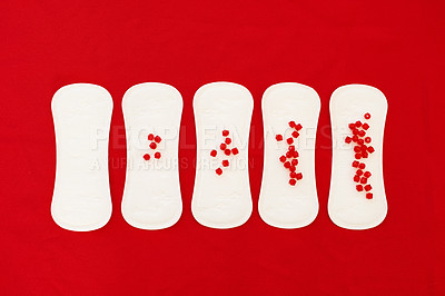 Buy stock photo Studio shot of sanitary pads placed in a row with an increasing amount of red beads on them against a red background