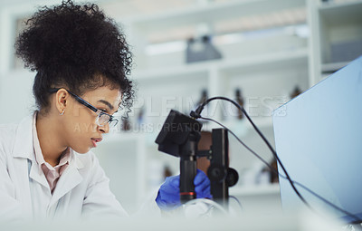 Buy stock photo Cropped shot of an attractive young female scientist working with a digital microscope in a laboratory