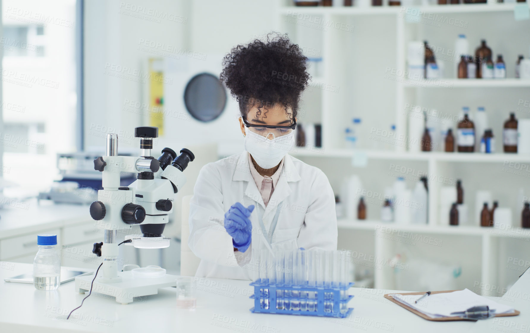 Buy stock photo Cropped shot of an attractive young female scientist working with test tubes in a laboratory