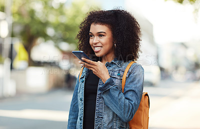 Buy stock photo Shot of an attractive young woman recording voice notes on her cellphone while out in the city
