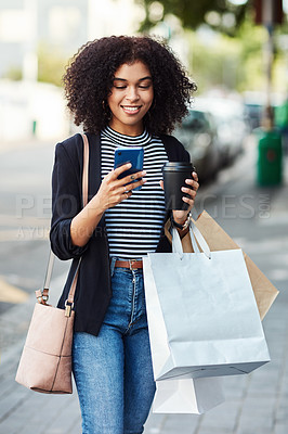 Buy stock photo Shot of an attractive young woman drinking coffee and using her cellphone while doing some shopping in the city