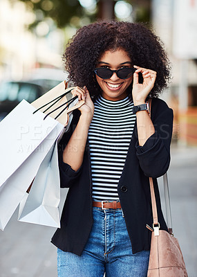 Buy stock photo Portrait of an attractive and stylish young woman carrying shopping bags in the city