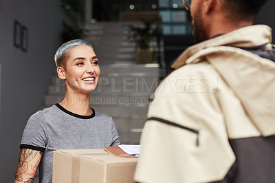 Buy stock photo Cropped shot of an attractive young woman smiling while receiving a package from a male courier at her home