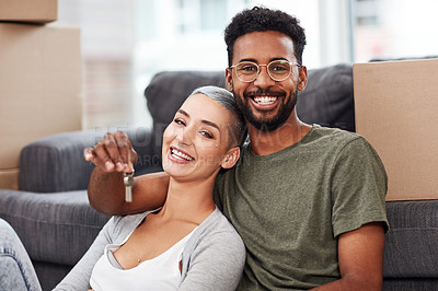 Buy stock photo Shot of a couple sitting together while holding the keys to their new home