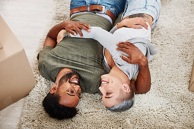 Buy stock photo Cropped shot of a young couple lying together on the carpet at home