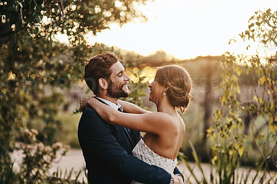 Buy stock photo Shot of a happy young couple standing together on their wedding day
