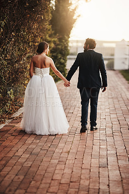 Buy stock photo Rearview shot of a couple walking together on their wedding day
