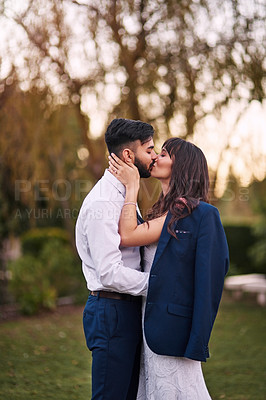Buy stock photo Cropped shot of an affectionate young bride kissing her groom while wearing his jacket on their wedding day