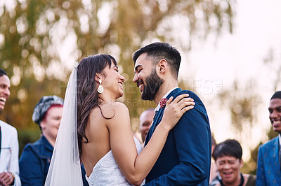 Buy stock photo Cropped shot of an affectionate young newlywed couple smiling at each other on their wedding day with their guests in the background