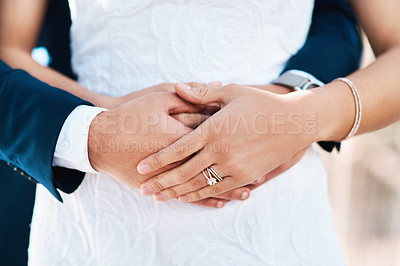 Buy stock photo Cropped shot of an unrecognizable bridegroom embracing his bride from behind while standing outdoors on their wedding day