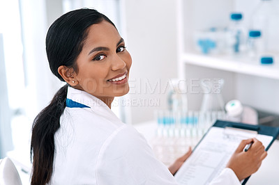 Buy stock photo Cropped portrait of an attractive young female scientist smiling while writing on a clipboard in a laboratory