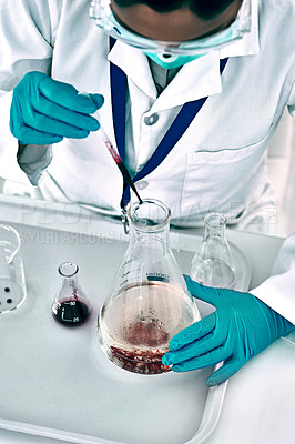 Buy stock photo High angle shot of an unrecognizable female scientist conducting an experiment with a liquid in a laboratory