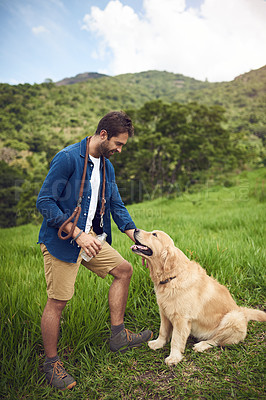 Buy stock photo Full length shot of a handsome young man standing with his golden retriever during a hike