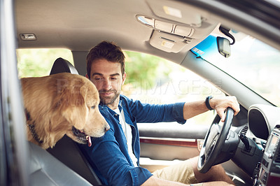 Buy stock photo Cropped shot of a handsome young man sitting in the car with his golden retriever during a road trip