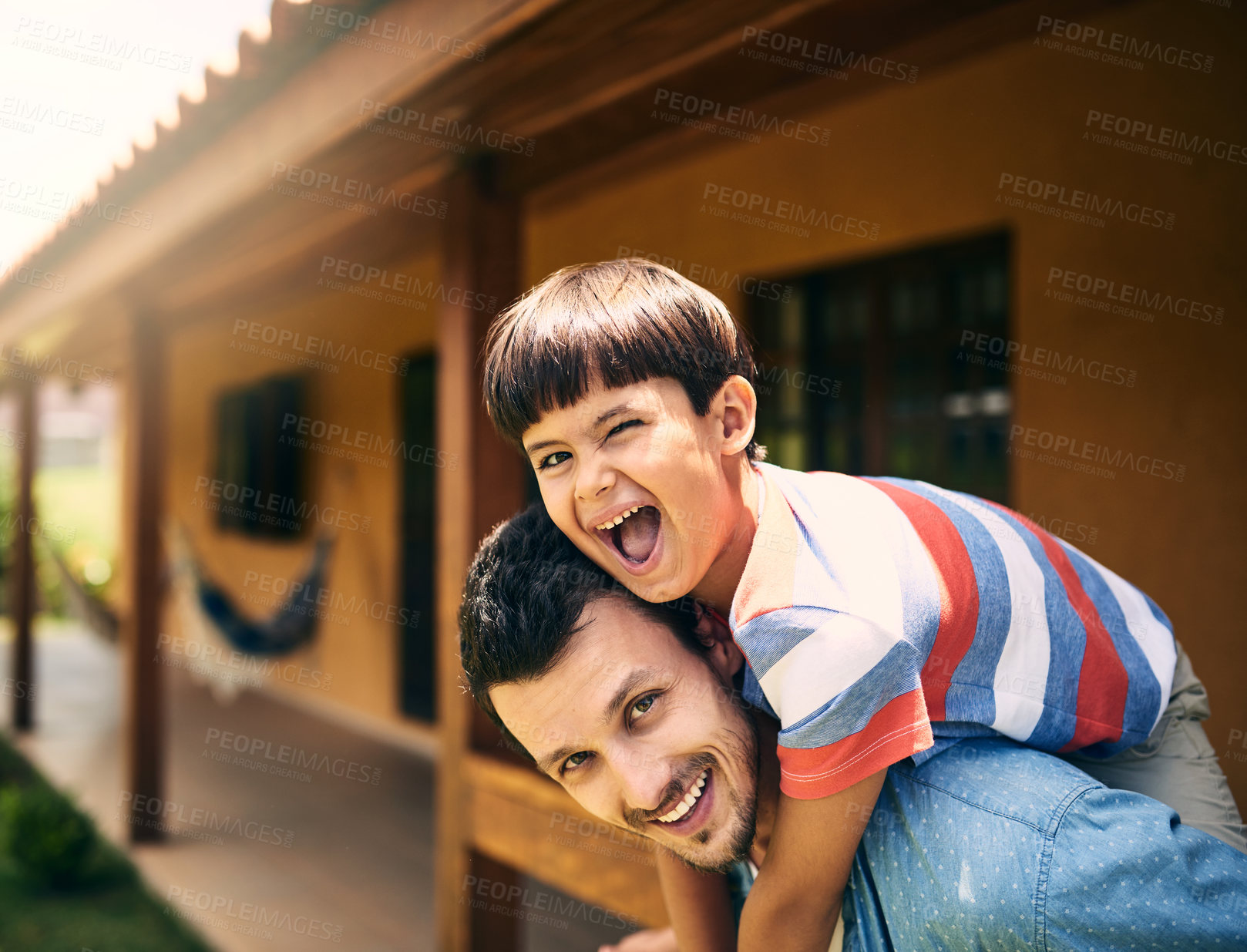 Buy stock photo Cropped portrait of an affectionate young father piggybacking his little son while standing in their backyard at home