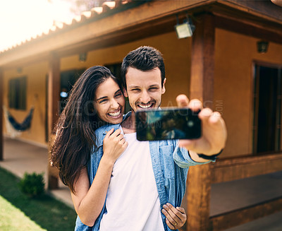Buy stock photo Cropped shot of an affectionate young couple taking a selfie together while standing in their backyard at home