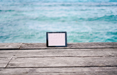 Buy stock photo Still life shot of a digital tablet placed on a boardwalk overlooking the ocean in Raja Ampat, Indonesia