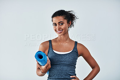 Buy stock photo Cropped shot of an attractive young woman posing with her yoga mat against a grey background
