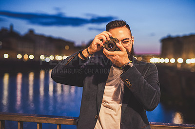 Buy stock photo Cropped portrait of a handsome young man standing and taking a picture with his camera while touring Italy at night