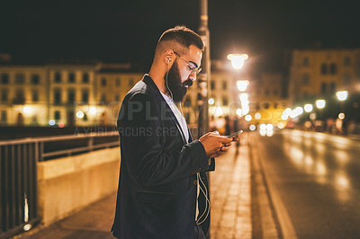 Buy stock photo Cropped shot of a handsome young man standing and wearing earphones while listening to music from his cellphone