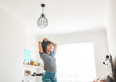 Buy stock photo Shot of a young woman dancing while wearing headphones in her bedroom