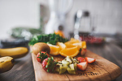 Buy stock photo Shot of fresh fruit on a chopping board in the kitchen