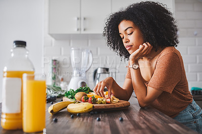 Buy stock photo Shot of a young woman looking unhappy while making a healthy snack with fruit at home
