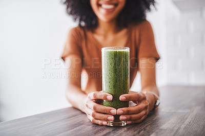 Buy stock photo Shot of a young woman enjoying a healthy smoothie at home