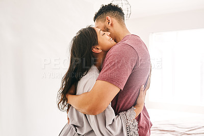 Buy stock photo Shot of a happy young couple embracing in their bedroom at home