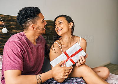Buy stock photo Shot of a young man surprising his wife with a gift in bed at home