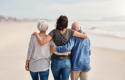 Buy stock photo Rearview shot of a young woman going for a walk along the beach with her elderly parents