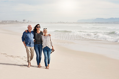 Buy stock photo Shot of a young woman going for a walk along the beach with her elderly parents