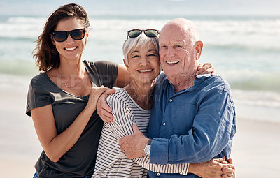Buy stock photo Shot of a young woman spending quality time with her elderly parents at the beach