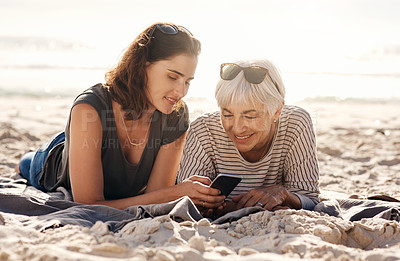 Buy stock photo Shot of a young woman using a smartphone with her elderly mother at the beach
