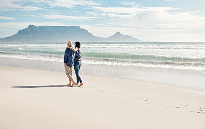 Buy stock photo Rearview shot of a young woman going for a walk along the beach with her elderly father
