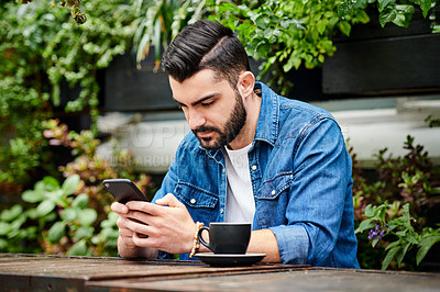 Buy stock photo Shot of a young man using a smartphone in a restaurant