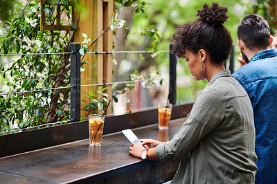 Buy stock photo Shot of a young woman using a smartphone at a restaurant