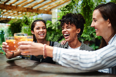 Buy stock photo Shot of a group of young women toasting with their drinks at a restaurant