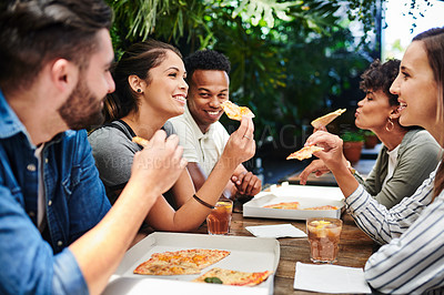 Buy stock photo Shot of a group of young friends having pizza at a restaurant