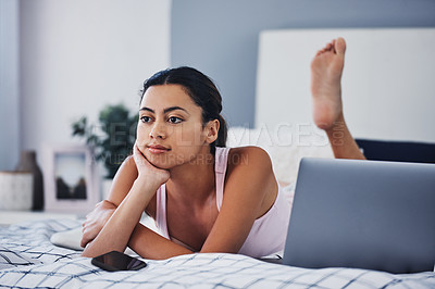 Buy stock photo Cropped shot of an attractive young woman lying on her bed and looking contemplative while at home alone