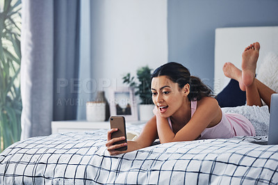 Buy stock photo Full length shot of an attractive young woman lying on her bed and taking a selfie with her cellphone