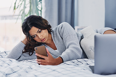 Buy stock photo Cropped shot of an attractive young woman lying on her bed and using her cellphone while home alone