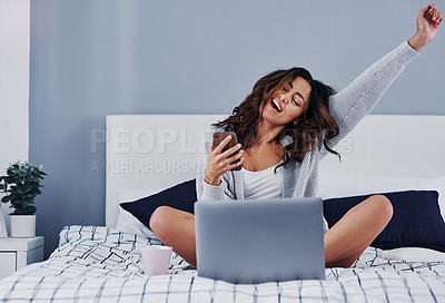 Buy stock photo Full length shot of an attractive young woman sitting at home and feeling excited while using her laptop