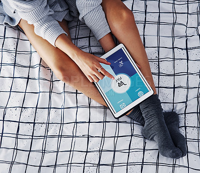 Buy stock photo High angle shot of an unrecognizable woman sitting on her bed and using a tablet at home alone