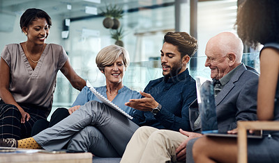 Buy stock photo Shot of a group of businesspeople planning and discussing ideas together in the lounge area inside their modern office