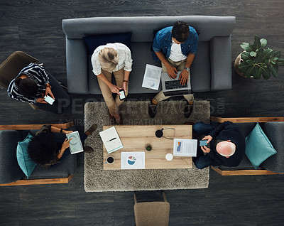 Buy stock photo High angle shot of a group of businesspeople using digital devices while having a meeting in an office