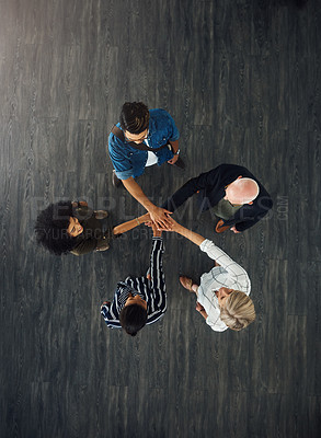 Buy stock photo High angle shot of a group of businesspeople joining their hands together in a huddle in an office