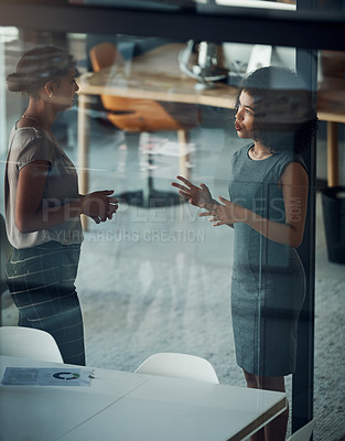 Buy stock photo Shot of two attractive young businesswomen having a discussion together at work